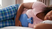 Woman Wearing Pajamas Suffering With Period Pain Lying In Bed With Hot Water Bottle