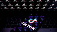 In this photo illustration, a TikTok logo is seen displayed