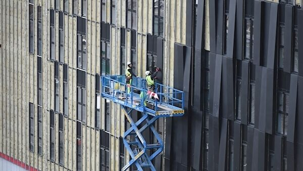 Workers position cladding on the exterior of the 200-bedroom Dean Hotel, under construction beside Kent Station, Cork. Picture: Larry Cummins
