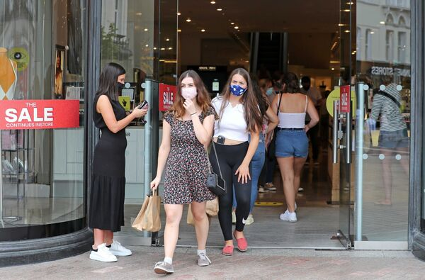 Brown Thomas staff member on the entrance with customers wearing facemasks, on Patrick Street.Picture: Jim Coughlan