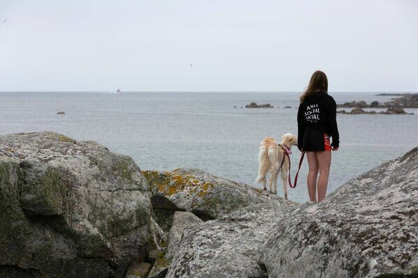 A girl and her dog look out to sea as the RNLI boat searched the waters for two misssing girls. Picture: Andy Newman.