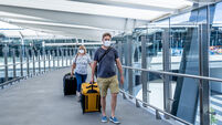 Senior woman and adult son wearing face mask at airport in fear of coronavirus and travel ban and international trips cancellati