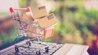 Online shopping and delivery service concept. Paper cartons in a shopping cart on a laptop keyboard, this image implies online s