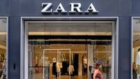 a woman exits Zara using a face mask that is mandatory in shops or open spaces in Barcelona