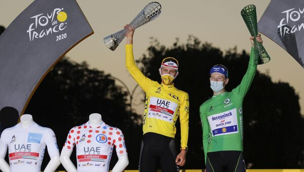 Slovenia's Tadej Pogacar, wearing the overall leader's yellow jersey, celebrates next to his two other jersey's, the best climber's dotted jersey and the best young rider's white jersey, as celebrates on the podium with Sam Bennett of Ireland, wearing the best sprinter's green jersey. Picture: AP Photo/Christophe Ena