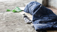 Homeless man sleeping in sleeping bag on cardboard