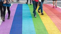 Gay pride flag crosswalk in Vancouver gay village with people crossing
