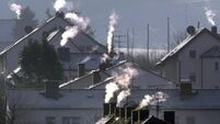 Smoke rises from the chimneys of houses on a cold and crisp winter's day in Nidderau, Germany, 21 December 2004. Photo: Frank Ru
