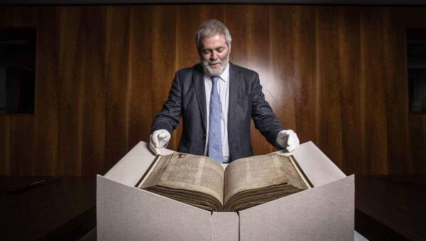 UCC Professor of Modern Irish Pádraig Ó Macháin pictured with The Book of Lismore which contains the only surviving translation in Irish of the travels of Marco Polo. Picture: Clare Keogh
