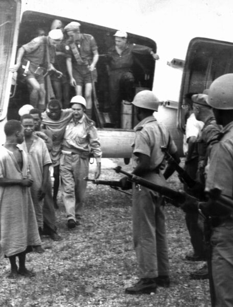 Niemba ambush in Congo, 1960. Cork man Dr. Beckett assisting an injured Baluba warrior from the plane in Albertville.
