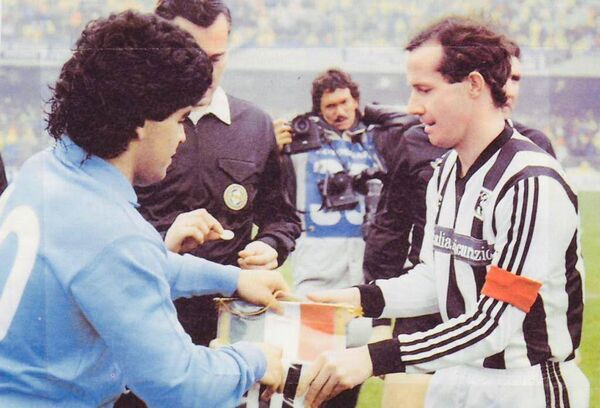 Meeting of Maestros: Ascoli's Liam Brady exchanges pennants with Napoli captain Diego Maradona