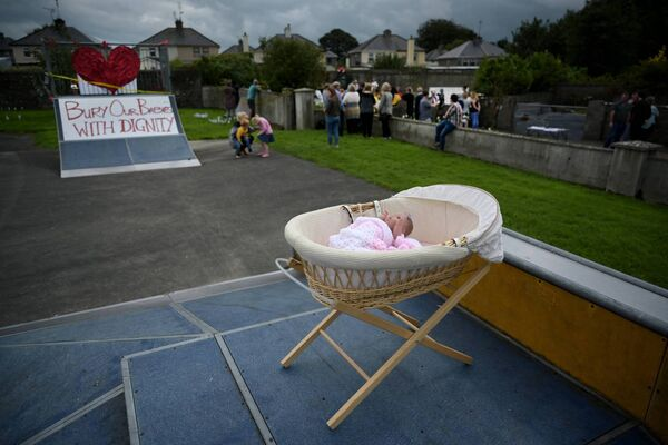 A baby doll and cot can be seen as a vigil is held at the Tuam Mother and Baby home mass burial site on August 25, 2019 in Tuam. Photo: Charles McQuillan/Getty Images)