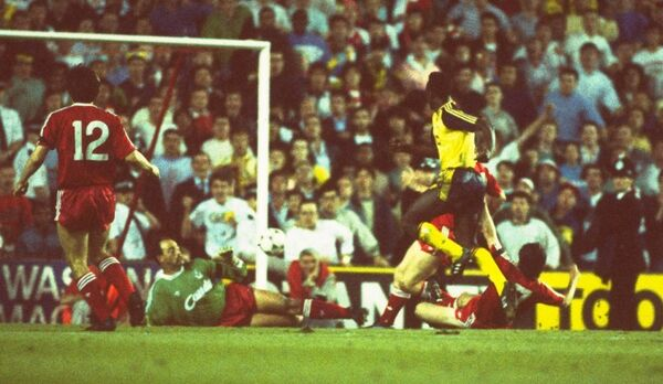 Michael Thomas of Arsenal (right) scores past goalkeeper Bruce Grobbelaar (centre) of Liverpool to score the title clinching goal during the League Division One match at Anfield in Liverpool, England. Arsenal won the match 2-0 and the championship. \ Mandatory Credit: Allsport UK /Allsport