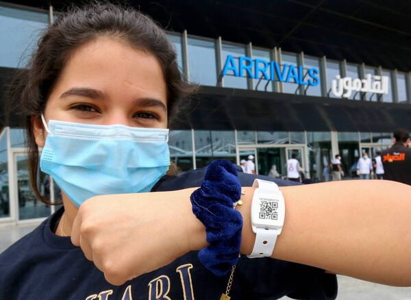 A Kuwaiti national, residing abroad, shows the tracking bracelet provided by authorities as she leaves at the Kuwait International airport in the capital upon her return as part of a repatriation plan on April 19, 2020, and ahead of being taken to mandatory home quarantine. Picture: Getty