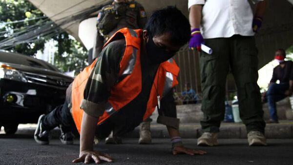 A resident does push-ups in May last year as a sanction for breaking large-scale social restriction regulations in Indonesia.