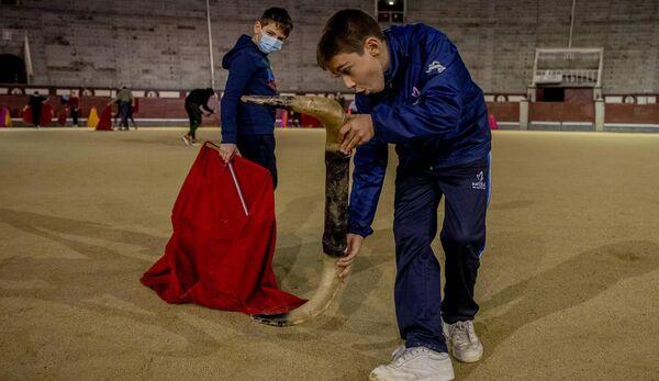 Nicholas Sanz Luna, 10, derecha, se presenta sosteniendo cuernos de plástico con Daniel en la escuela taurina de la plaza de toros de Las Ventas en Madrid, España.