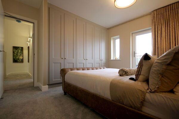 After: Turning a bedroom into a tech-free spot, promoting comfort, relaxation and sleep involves curtains to block out light, a good mattress, linens and candles.