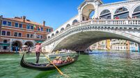 Gondola with tourists on Gran Canal with Rialto Bridge, Venice
