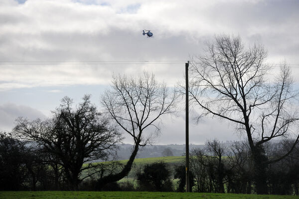Garda helicopter overhead at the scene where the third body was found after a manhunt in North Cork this morning. Picture: Larry Cummins