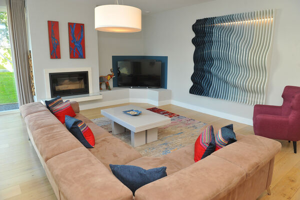 The family room /TV room with wall-mounted, painted plywood sculpture created by the homeowner.
