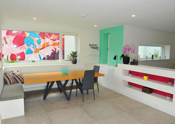 The kitchen-dining area with painted mural on exterior boundary wall visible from the window.