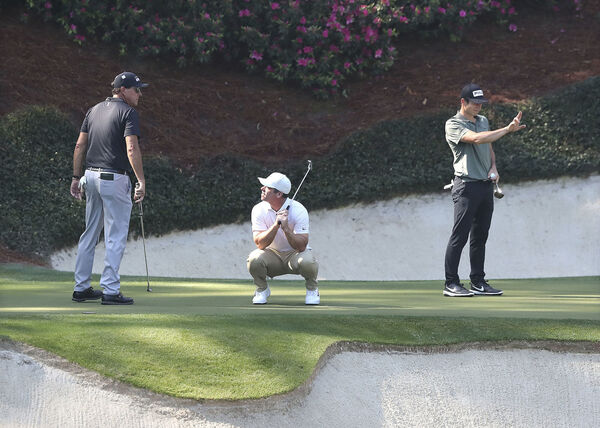Phil Mickelson (from left) looks on as Paul Casey reacts to just missing his birdie putt while Viktor Hovland lines his putt up on the 12th green during their practice round for the Masters at Augusta National. (Curtis Compton/Atlanta Journal-Constitution via AP)