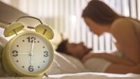 The clock on the background of the couple in the bed