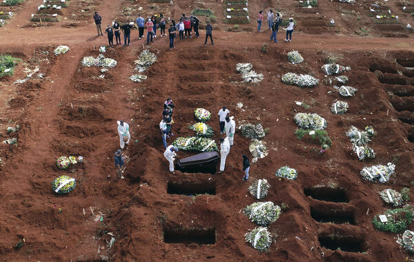 Cemetery workers wearing protective gear lower the coffin of a person who died from complications related to Covid-19 into a gravesite at the Vila Formosa cemetery in Sao Paulo, Brazil.  Picture: AP Photo/Andre Penner