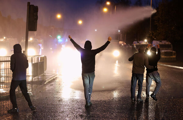 The PSNI use a water cannon on youths on the Springfield road, during unrest in Belfast.