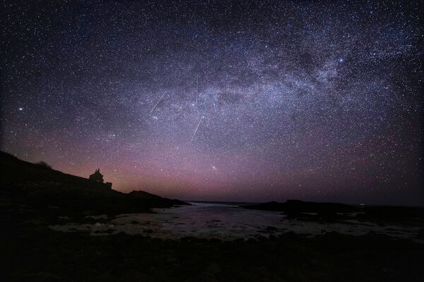 The Milky Way and Lyrid meteors falling through the sky at the Bathing House near Howick, Northumberland, as the Lyrid meteor shower reached its peak in 2020