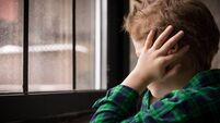 Little boy standing behind the window in sad mood. Sad Teenager looking in the Window and closing his ears with hands. Unhappy c