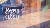 Woman Holding up a shop sign saying: Sorry we're Closed