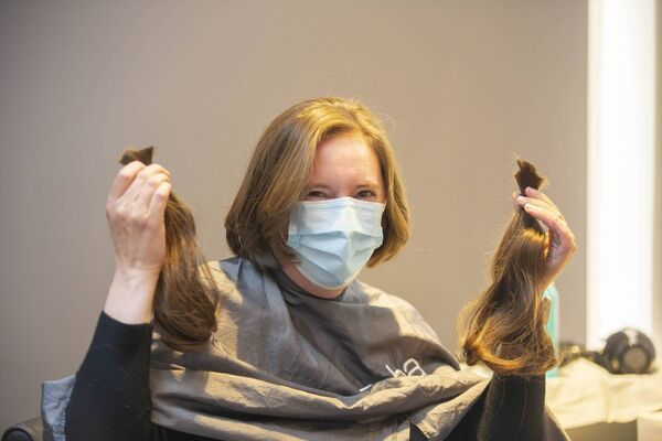 Mary Crispie from Cork getting her hair cut for the first time in months while raising fund for the Rapunzel charity in Zeba, Dublin, on Monday. Picture: Gary Ashe