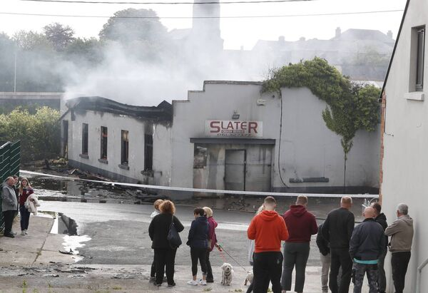 Onlookers at the scene of the fire that destroyed the             building. Picture: Liam Burke/Press 22