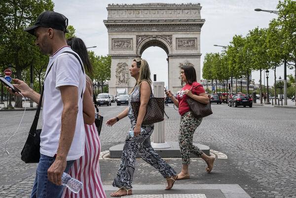 Ludzie przechodzą w czwartek przez Pola Elizejskie w Paryżu.  W środę Francja złagodziła kilka ograniczeń Covid.  Plik obrazu: AP Photo / Michel Euler