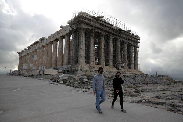 Odwiedzający w maskach na twarz wspinają się na Akropolu, z Partenonem w tle w Atenach.  Plik obrazu: AP Photo / Thanassis Stavrakis