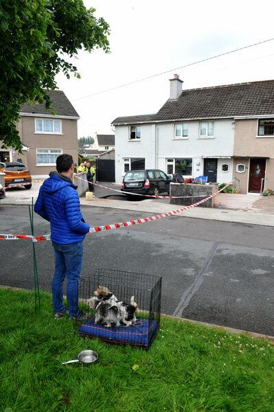Pemilik rumah Gary O'Donovan hanya dapat melihat di tempat kejadian pada pagi Ahad dari lubang lubang di jalan masuk kediamannya di Blackrock.  Gambar: Larry Cummins