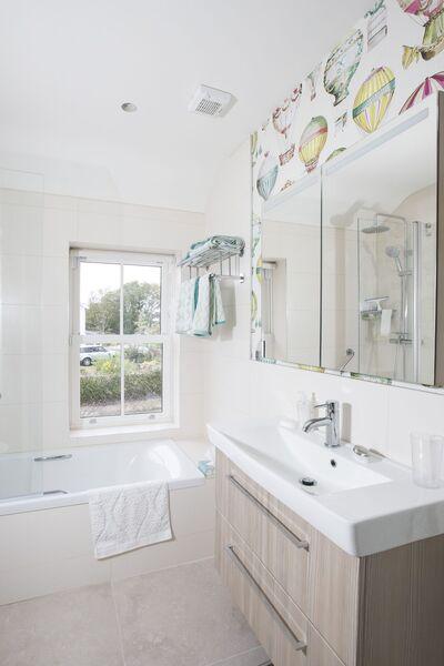 Un espace salle de bain pratique est fini avec un papier peint amusant en montgolfière derrière le meuble sous-lavabo.