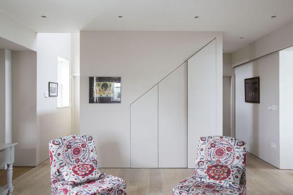 Le rangement est une caractéristique importante de la maison, mais bien dissimulé grâce à une conception réfléchie et à de belles armoires, comme on le voit ici dans un agencement sous les escaliers où les produits de nettoyage et l'aspirateur sont sécrétés.