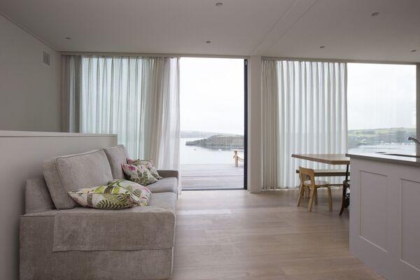 Des portes vitrées coulissantes du sol au plafond donnent accès depuis la cuisine ouverte, la salle à manger et le salon à la deuxième des trois terrasses.