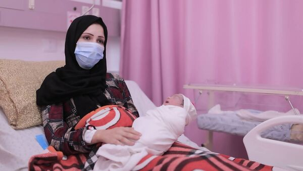 Mervat Al-Buhtaimi with his baby Sedra.  Women's pregnancies were affected by heavy bombardment of the area by Israeli forces in May.  Picture.  ActionAid through Palestine ActionAid Ireland