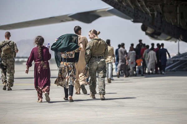 A Sailor with the 24th Marine Expeditionary Unit walks with a family during ongoing evacuations at Hamid Karzai International Airport, Kabul, Afghanistan, Tuesday, August 24, 2021. Photo: Sgt.  Samuel Ruiz / US Marine Corps via AP