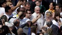 Pope poses for 'selfies' with young