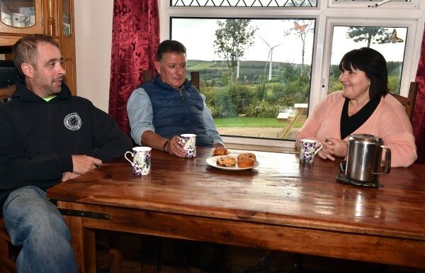 Sean and Catherine Harris with neighbour Kenneth Geary, left, in the kitchen of their house at Glenforan, Ballyduff Upper, Co Waterford, with the wind turbines visible through the window. Picture: Eddie O'Hare