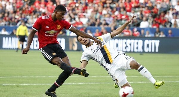 Manchester United's Marcus Rashford, left, shoots past LA Galaxy's Hugo Arellano to score his second goal in the friendly match clash in Los Angeles at the weekend. Jose Mourinho expects Rashford to score more consistently next season. Picture: Jae C Hong