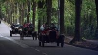 Visiting party from Germany driven along Centre Park Road in Ford Model T 's