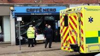 Minor injuries as Porsche crashes through front of coffee shop