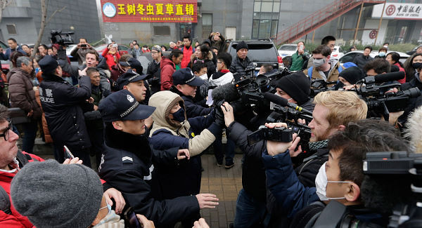 Police officers push away supporters of rights lawyer Pu Zhiqiang and foreign journalists near the Beijing Second Intermediate People's Court in Beijing today. Pic: AP